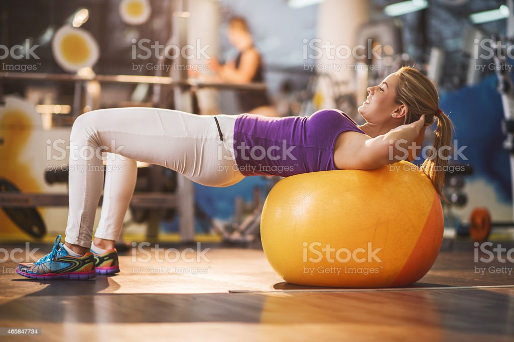 Smiling woman doing sit-ups on fitness ball. stock photo