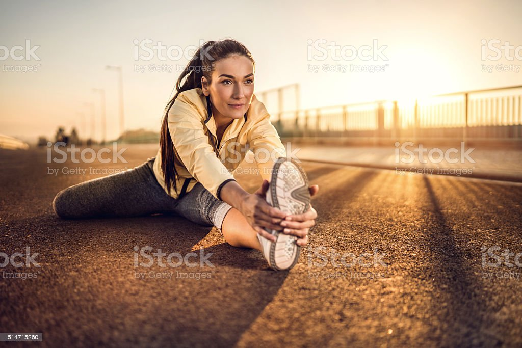 Smiling woman doing stretching exercise at sunset. stock photo