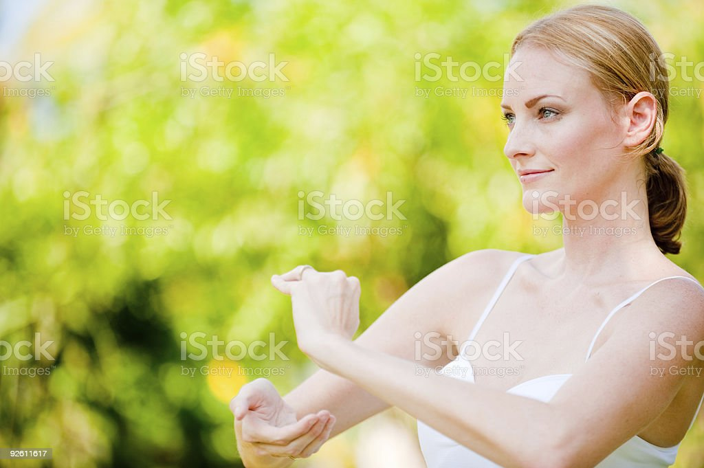 Smiling woman doing Tai Chi outdoors royalty-free stock photo