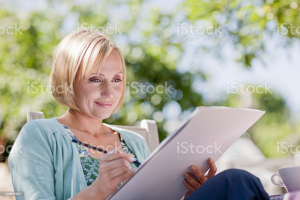 Smiling woman drawing on sketch pad outdoors royalty-free stock photo
