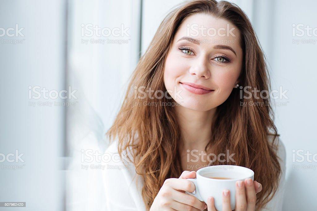 Smiling woman drinking coffe near the window stock photo
