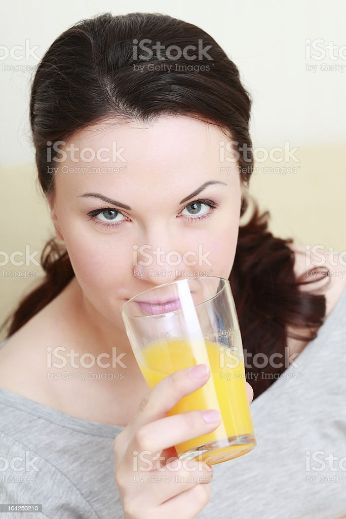 Smiling woman drinking orange juice stock photo
