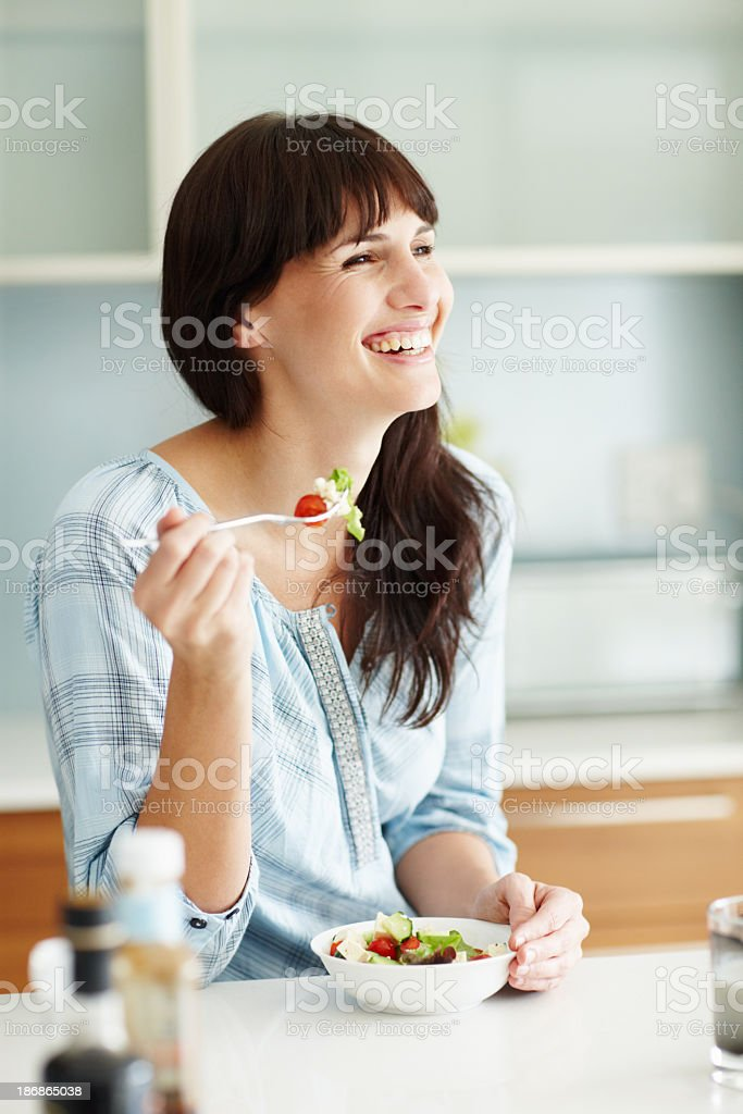 Smiling woman eating a bowl of salad at the table stock photo