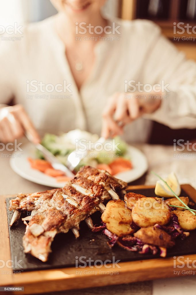 Smiling woman eating in restaurant stock photo