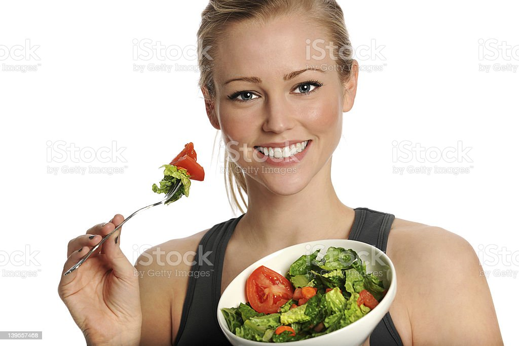 Smiling woman eating salad with tomatoes royalty-free stock photo