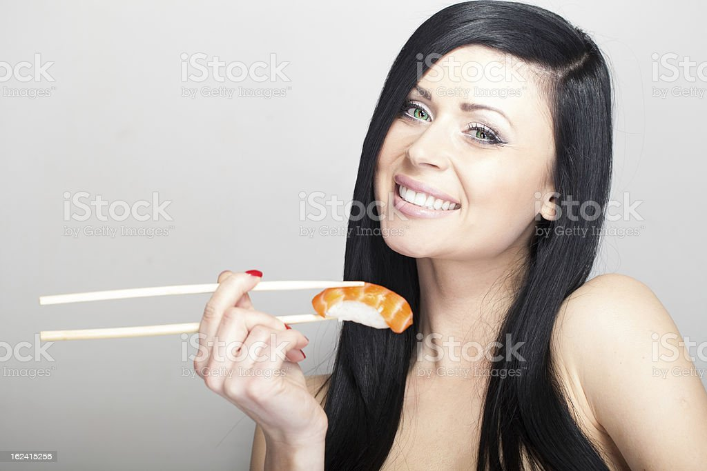 smiling woman eating salmon sushi royalty-free stock photo
