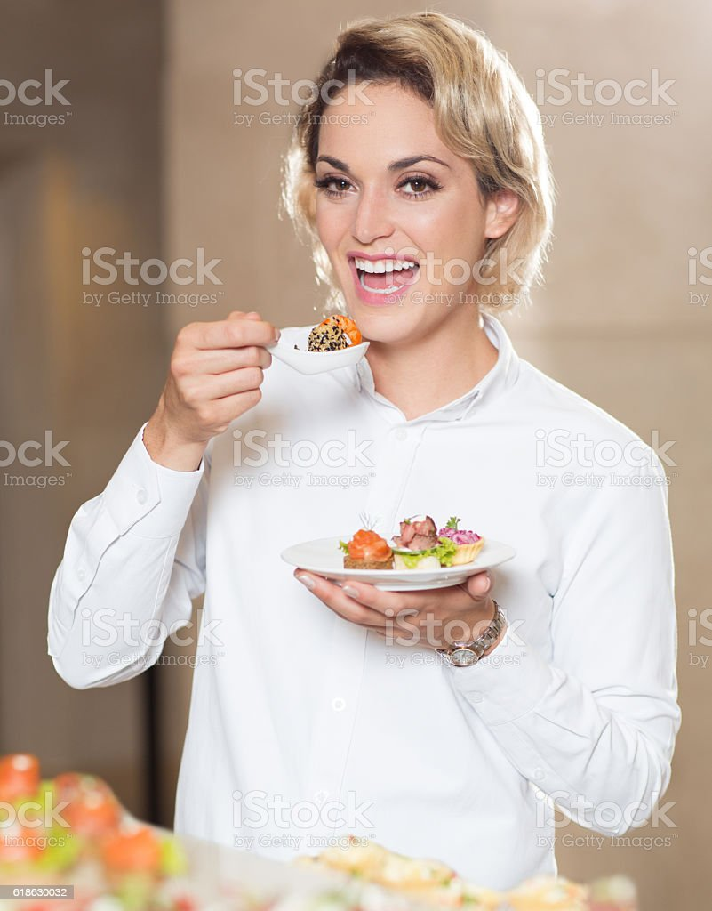 Smiling Woman Eating Snacks at Buffet Table stock photo