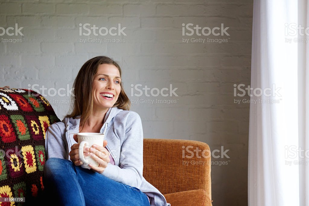 Smiling woman enjoying cup of tea at home stock photo