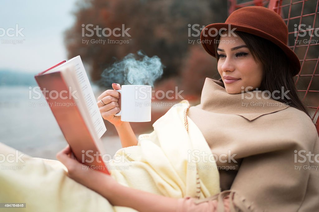 Smiling woman enjoying in a book and hot drink outdoors. stock photo