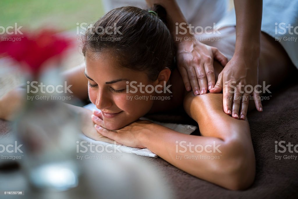 Smiling woman enjoying in a relaxing massage at the spa. stock photo