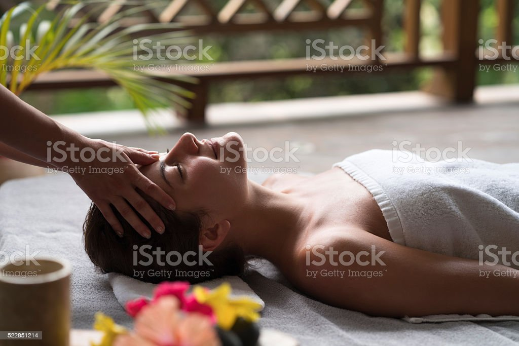 Smiling woman enjoying in head massage with her eyes closed. stock photo
