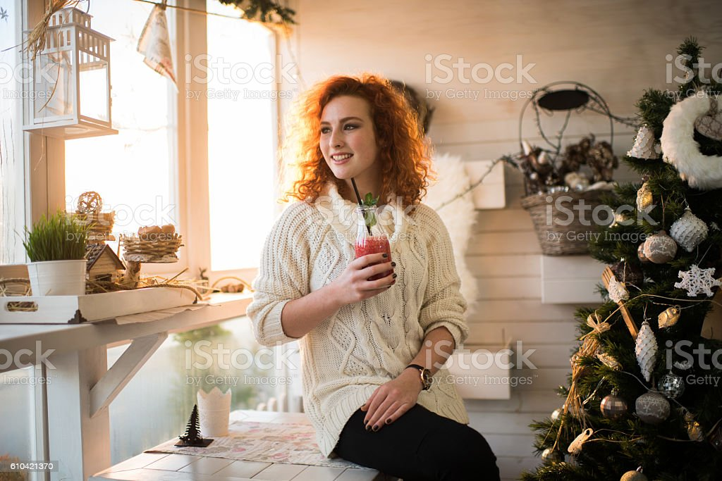 Smiling woman enjoying in red smoothie on New Year's Day. stock photo