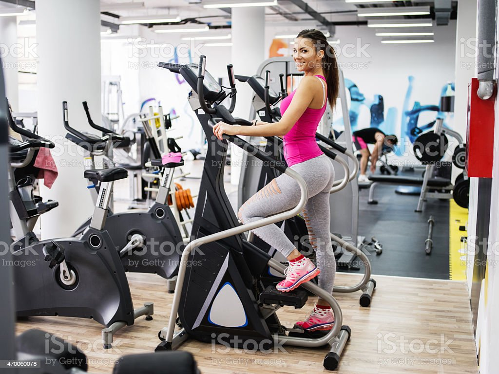 Smiling woman exercising on stepper machine in a health club. stock photo