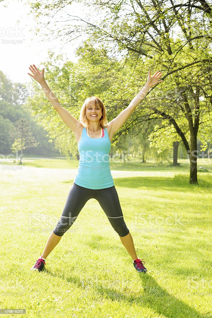 Smiling woman exercising outside stock photo