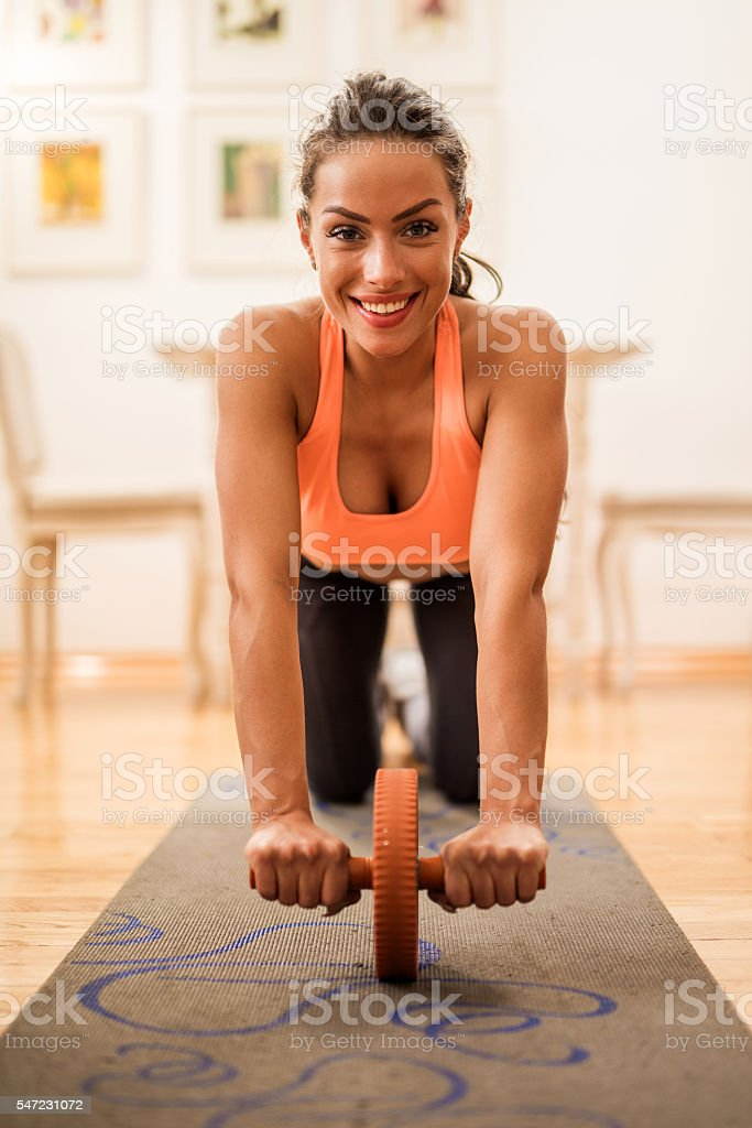 Smiling woman exercising with abdominal muscle wheel at home. stock photo