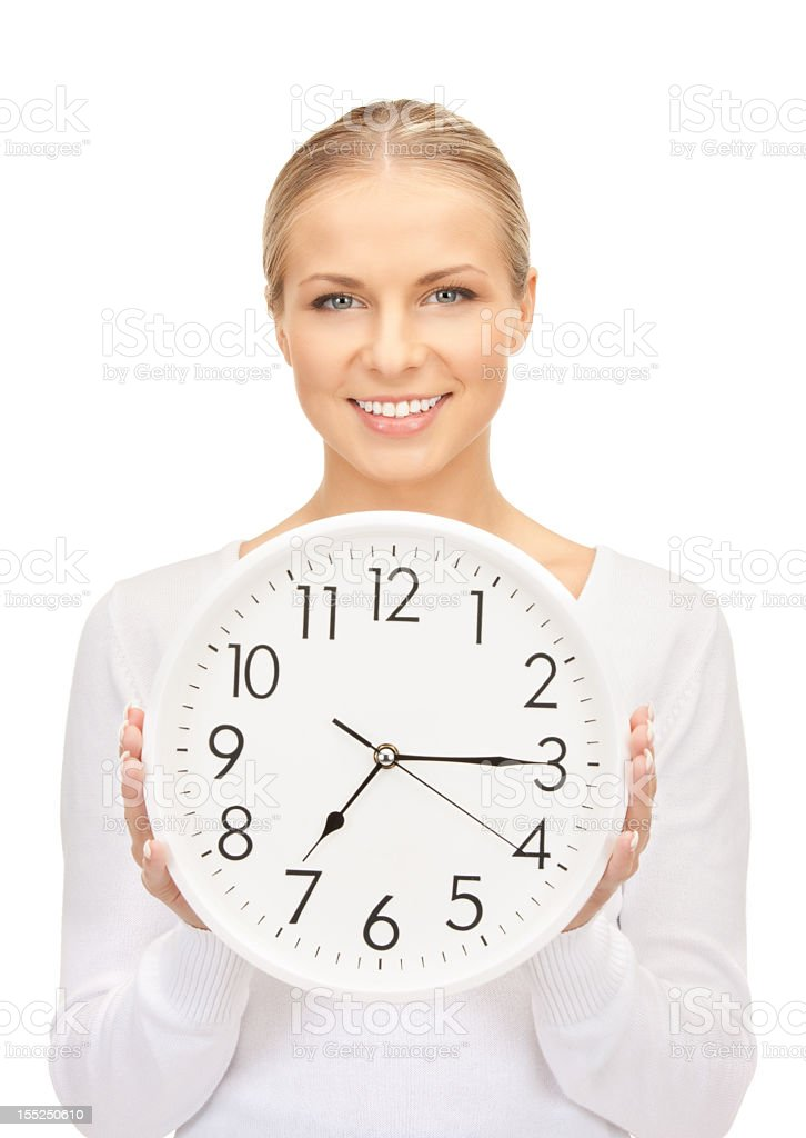 Smiling woman facing front holding white clock royalty-free stock photo