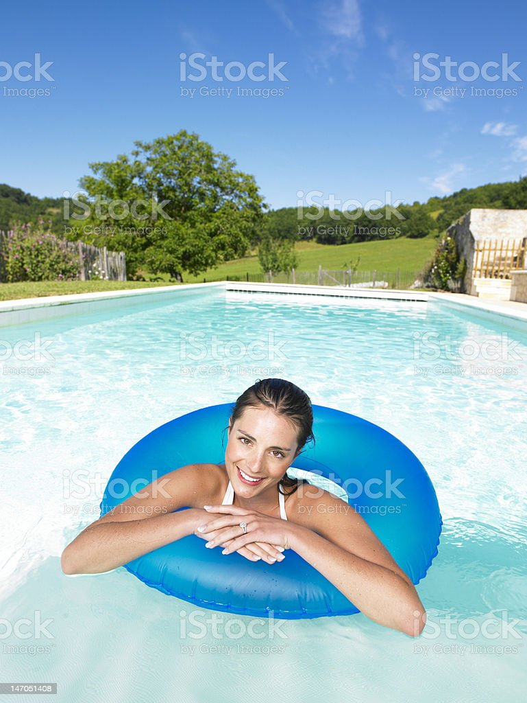 Smiling Woman Floating in Pool royalty-free stock photo