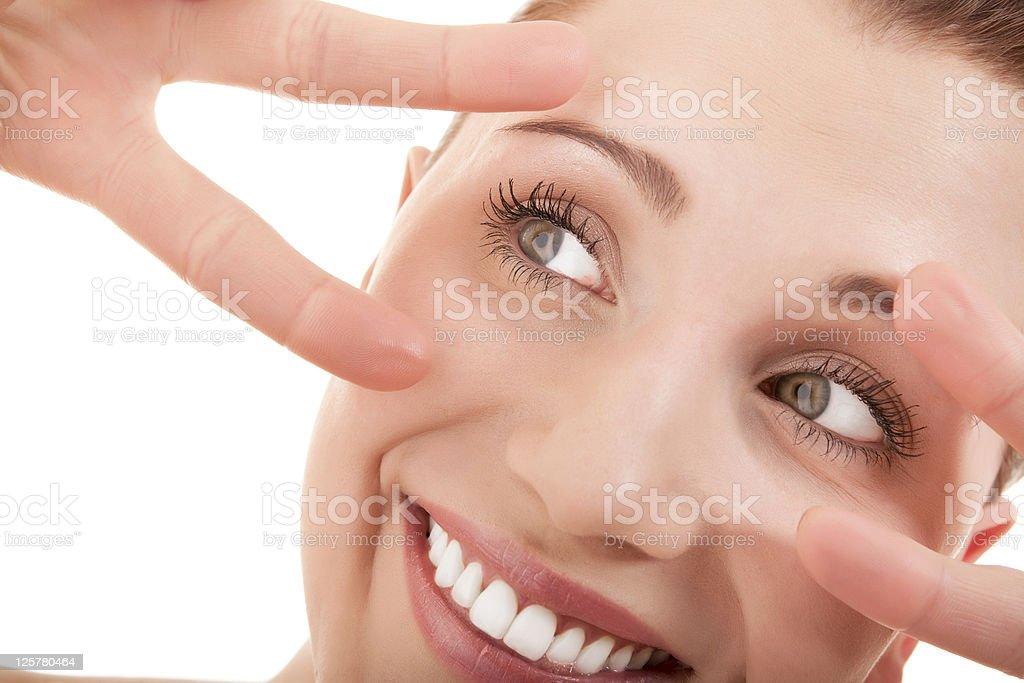 Smiling woman framing her eyes stock photo