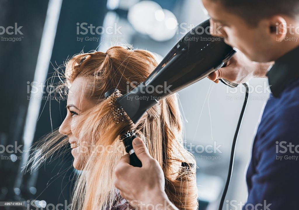 Smiling woman getting her hair styled and hair salon. stock photo