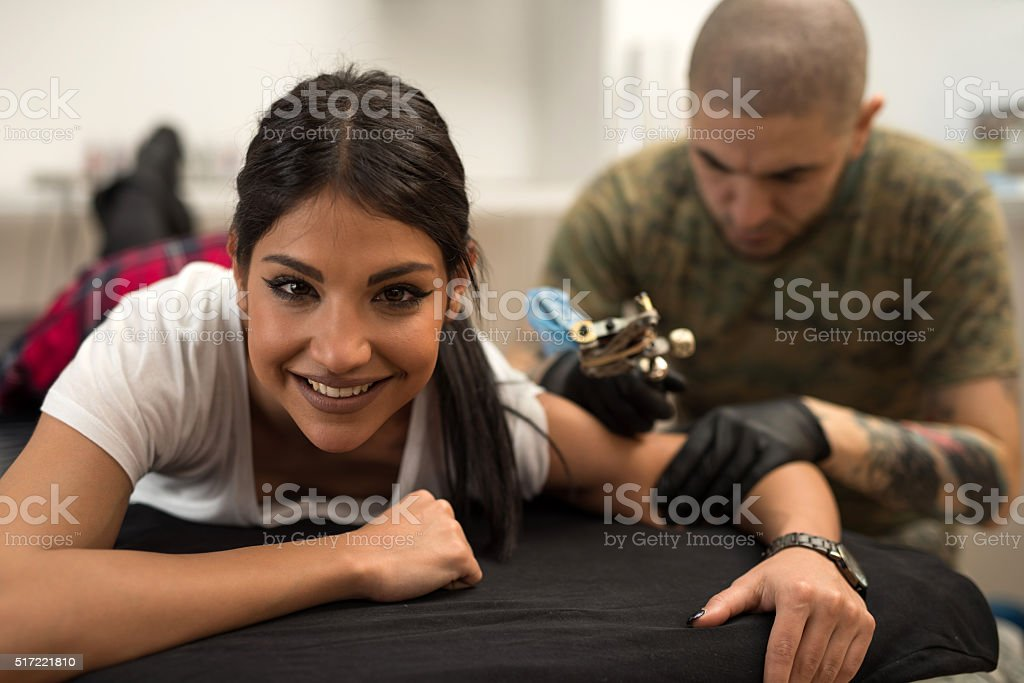 Smiling woman getting tattoo and looking at camera. stock photo