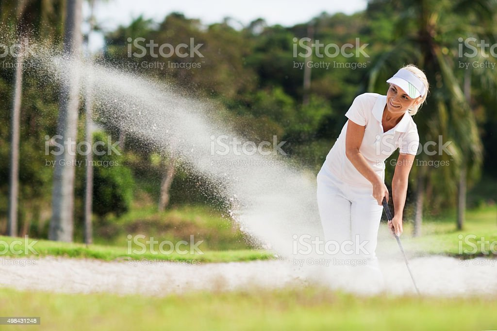 Smiling woman golf player in sand trap. stock photo