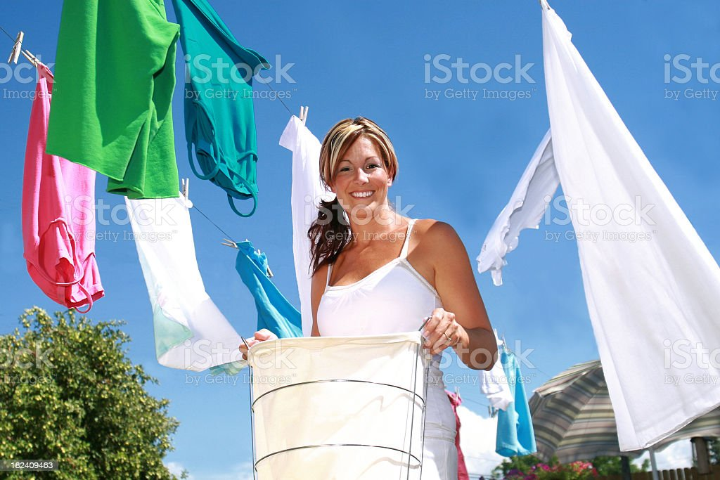 Smiling woman hanging laundry on a clothesline stock photo