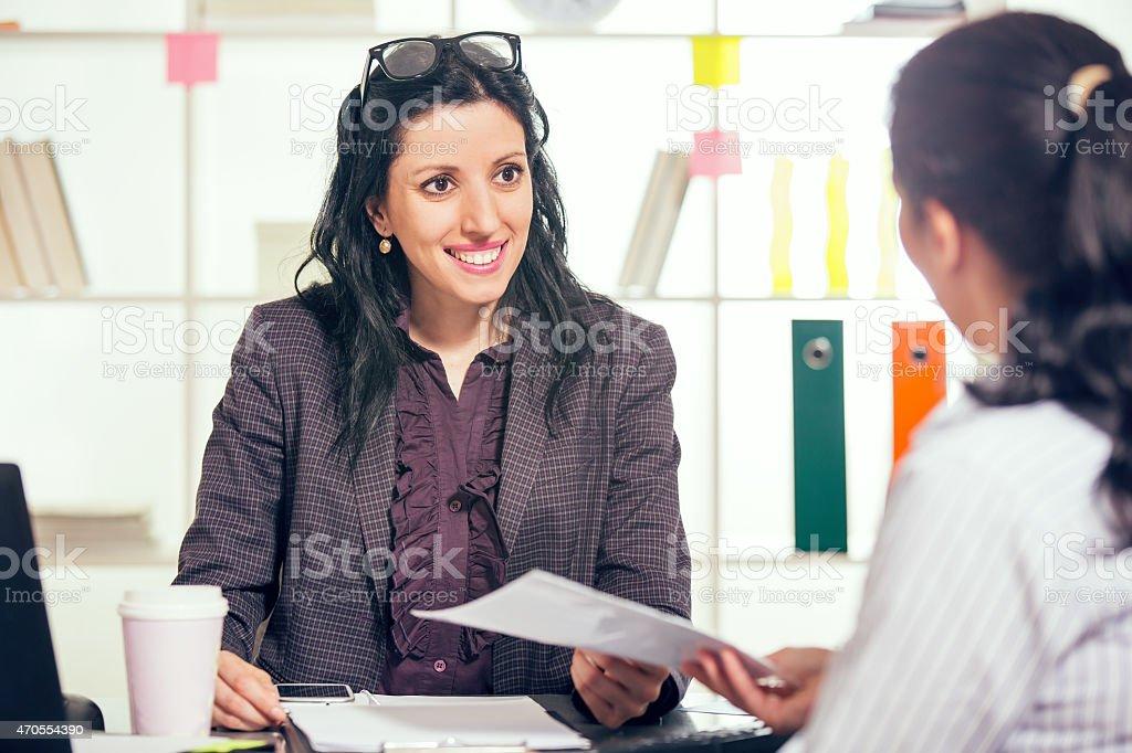 Smiling woman having job interviews and receiving portfolios stock photo