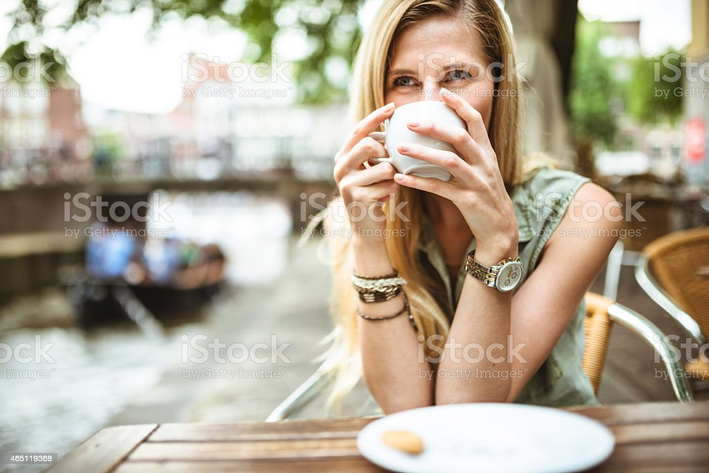 Smiling woman holding a coffee cup stock photo