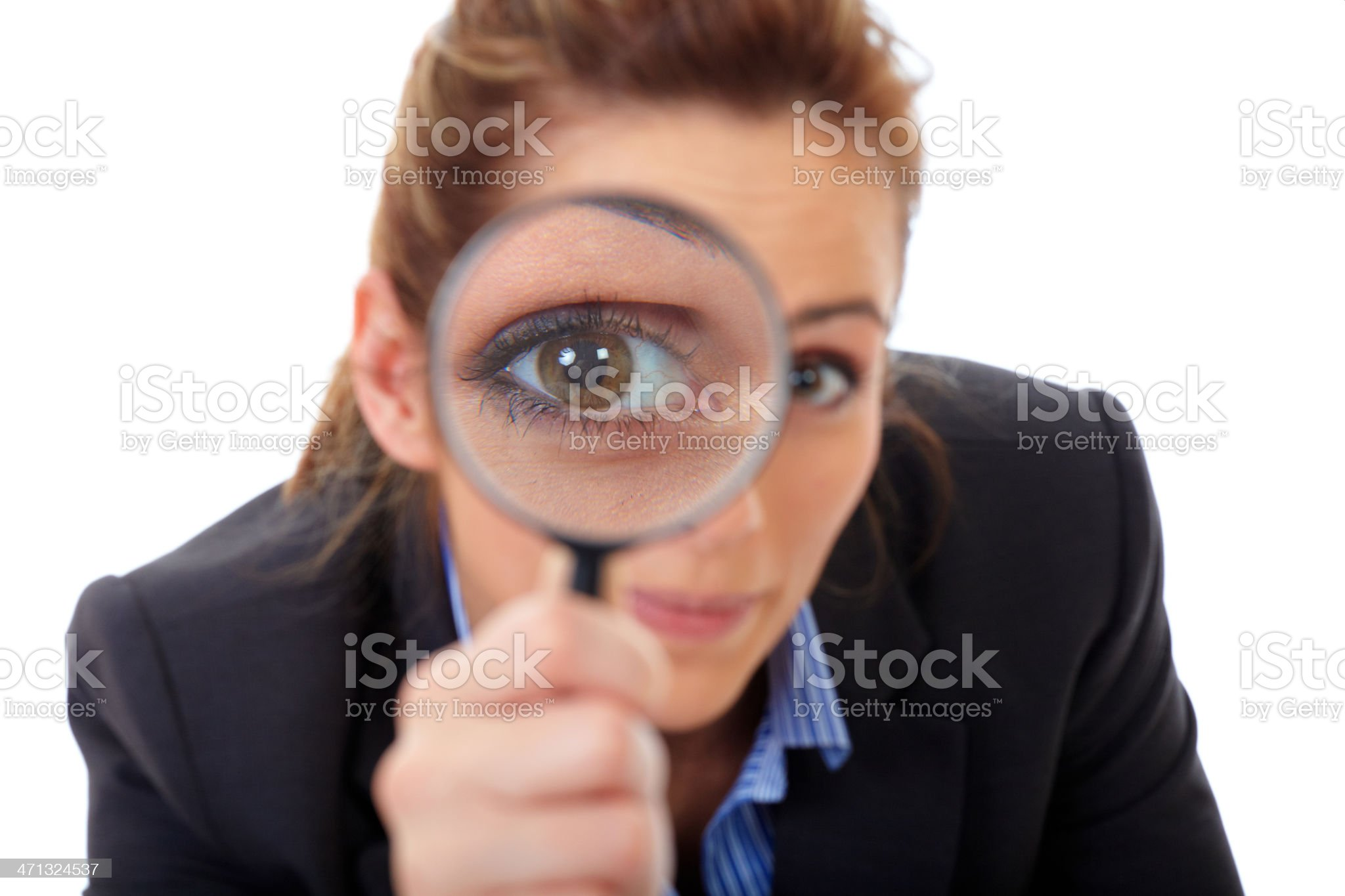 Smiling woman holding a magnifying glass over one eye royalty-free stock photo
