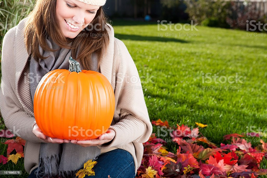 Smiling woman holding a pumpkin royalty-free stock photo