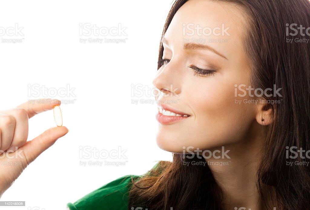 Smiling woman holding a single Omega 3 fish gel capsule stock photo