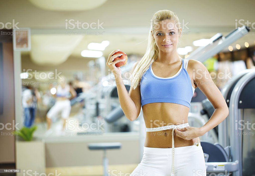 Smiling woman holding an apple in gym. royalty-free stock photo