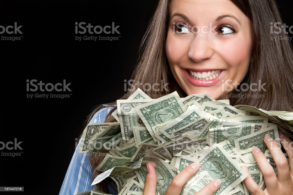 Smiling woman holding armful of cash stock photo