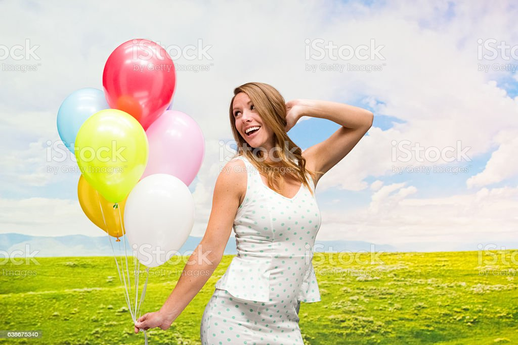 Smiling woman holding balloons outdoors stock photo