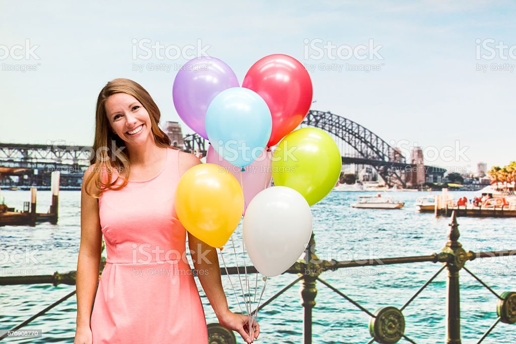 Smiling woman holding balloons stock photo