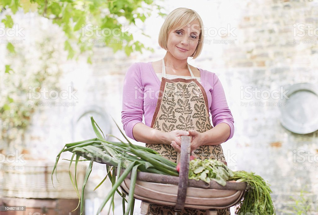Smiling woman holding basket of fresh vegetables royalty-free stock photo