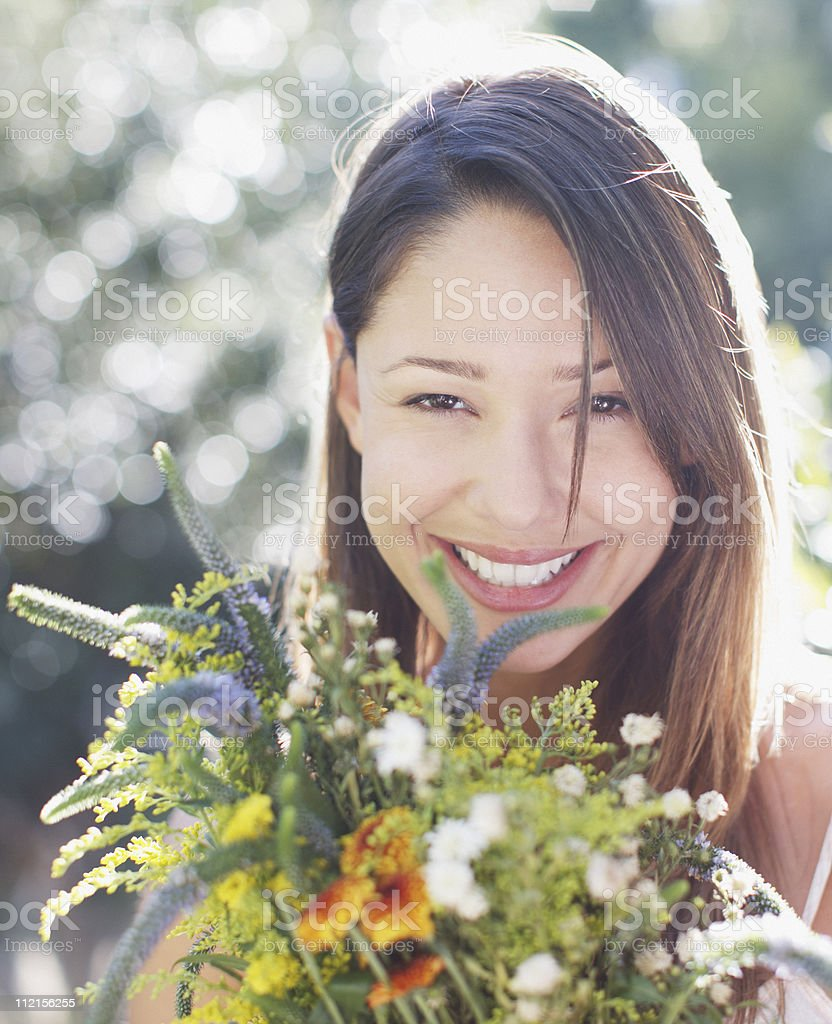 Smiling woman holding bouquet of flowers royalty-free stock photo
