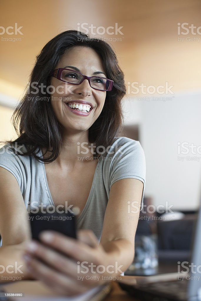 Smiling woman holding cell phone royalty-free stock photo