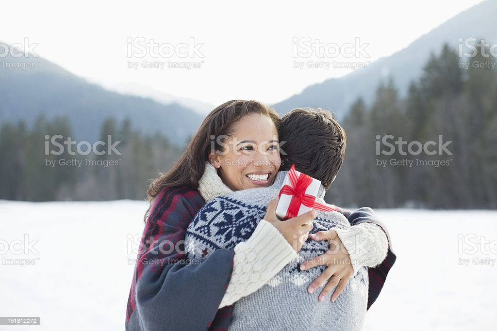 Smiling woman holding Christmas gift and hugging man in snow royalty-free stock photo