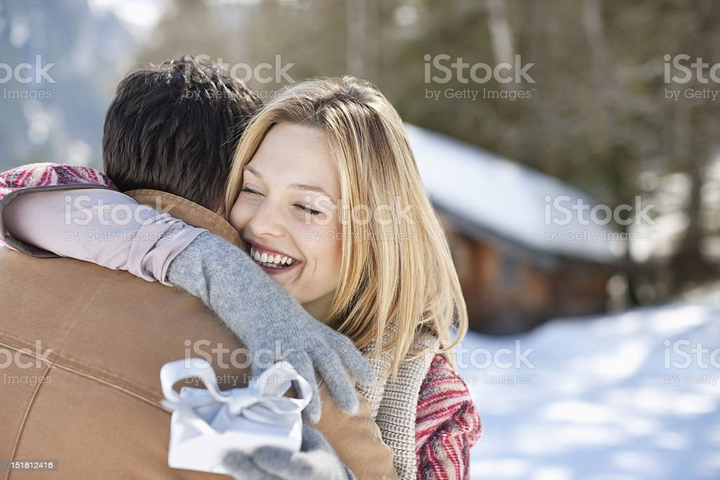 Smiling woman holding Christmas gift and hugging man in snowy field stock photo