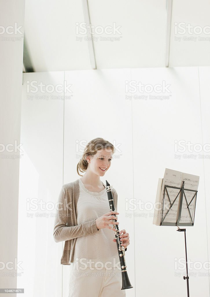 Smiling woman holding clarinet and looking at sheet music royalty-free stock photo