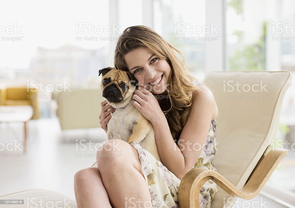 Smiling woman holding cute, small dog on lap stock photo