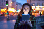 Smiling woman holding digital tablet on street by night