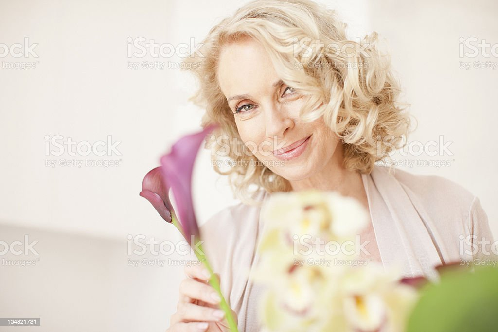 Smiling woman holding flowers royalty-free stock photo