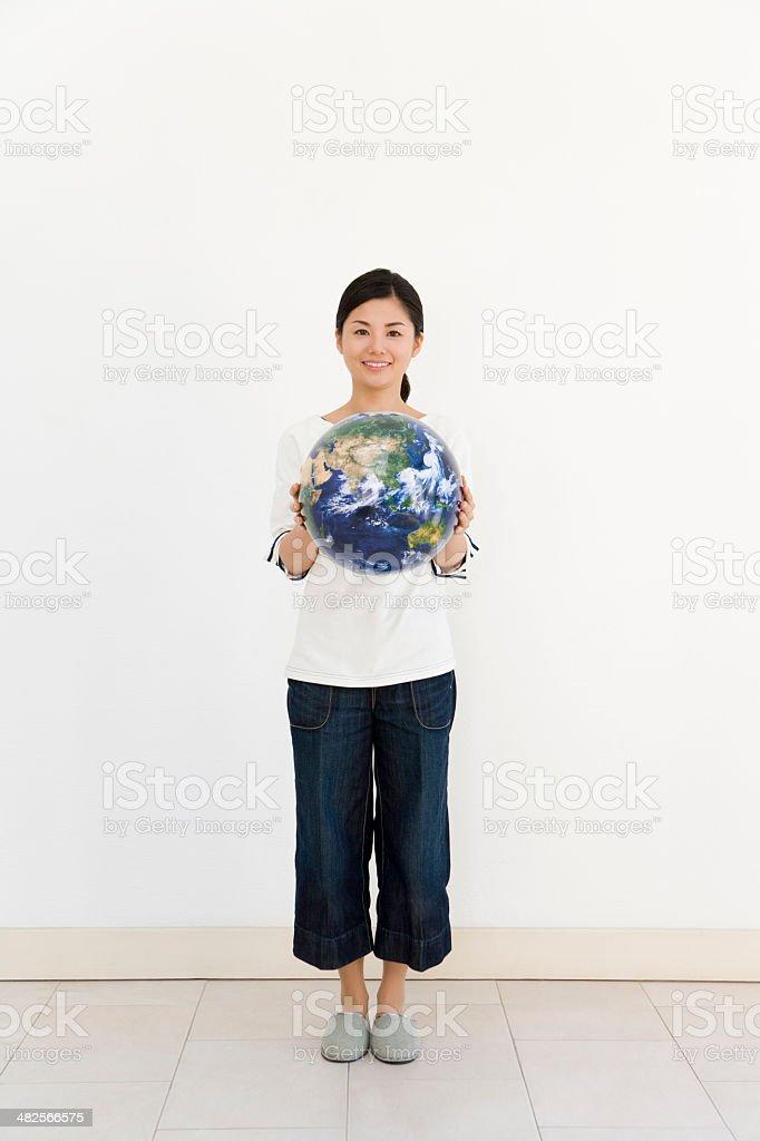 Smiling woman holding globe stock photo