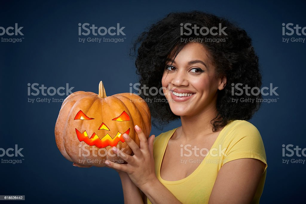 Smiling woman holding Halloween pumpkin stock photo