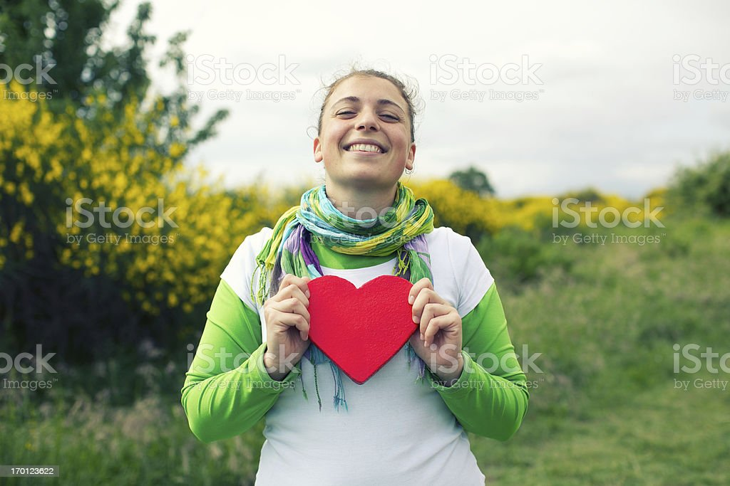Smiling woman holding heart stock photo