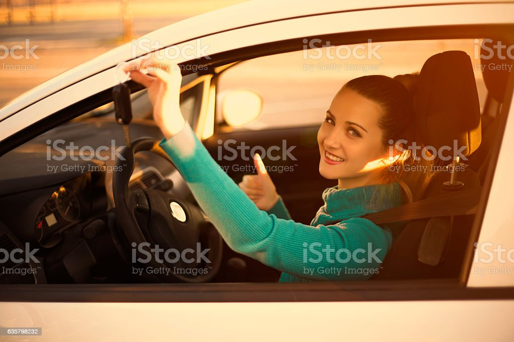 Smiling woman holding keys to new car at sunset stock photo