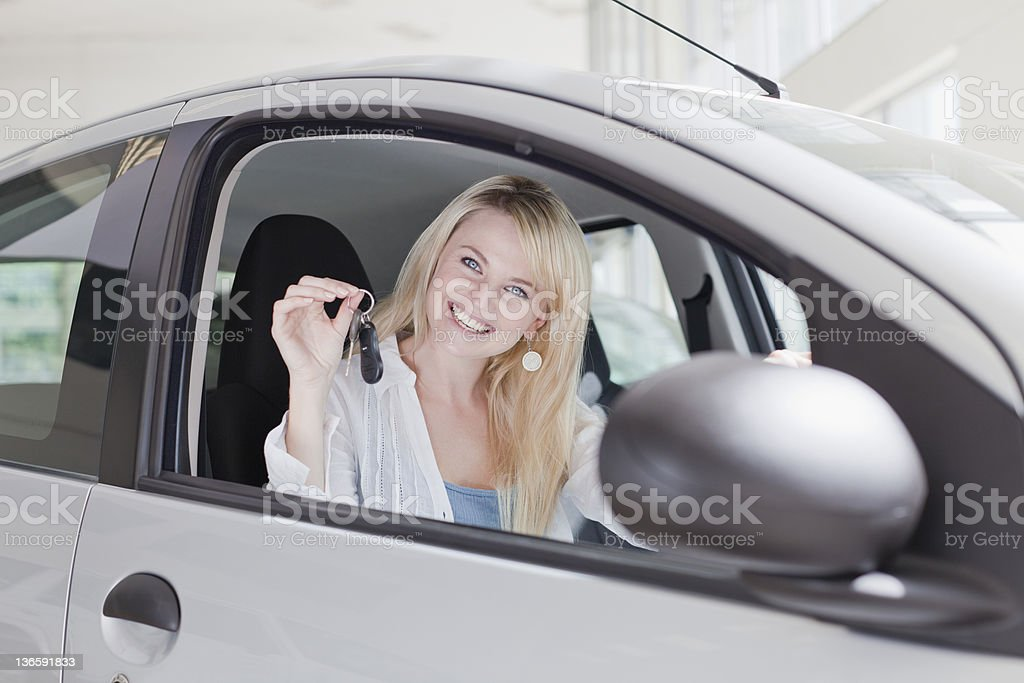 Smiling woman holding keys to new car stock photo