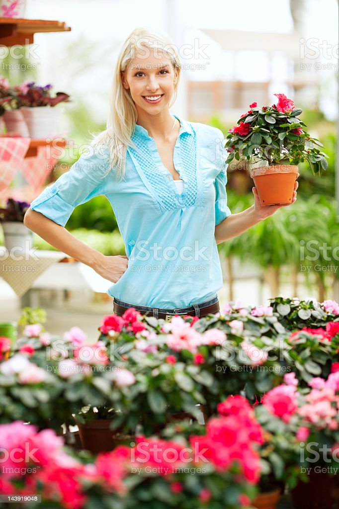 Smiling woman holding plant in a flowers shop royalty-free stock photo